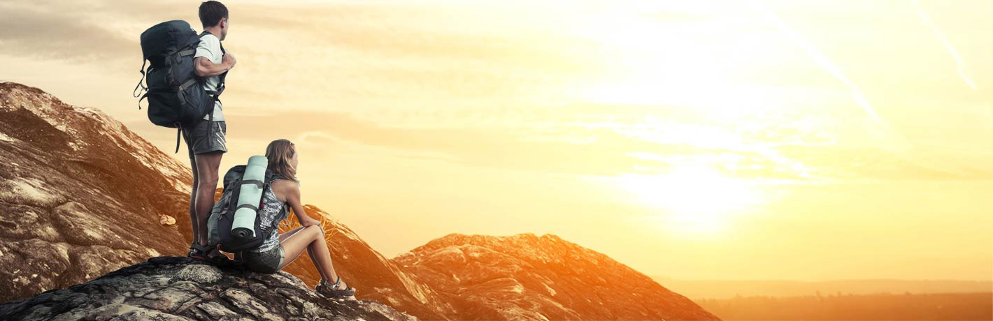 Image of young hiking couple looking at sunrise from mountaintop.