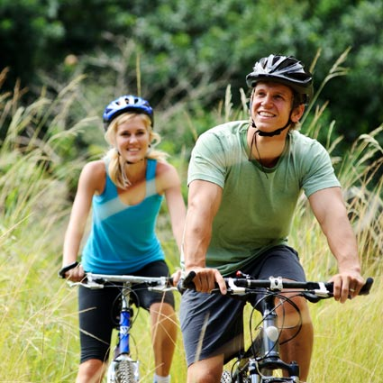 Young couple cycling after successful surgery.